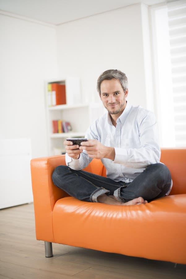 Sonrisa atractiva y teléfono del hombre en un sofá imagen de archivo
