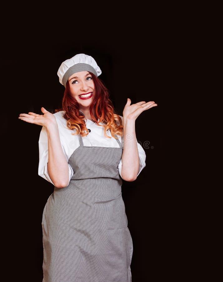 Sonrisa blanca aislada uniforme joven de la emoción del sombrero del delantal del fondo del negro de la mujer del cocinero del co imagen de archivo