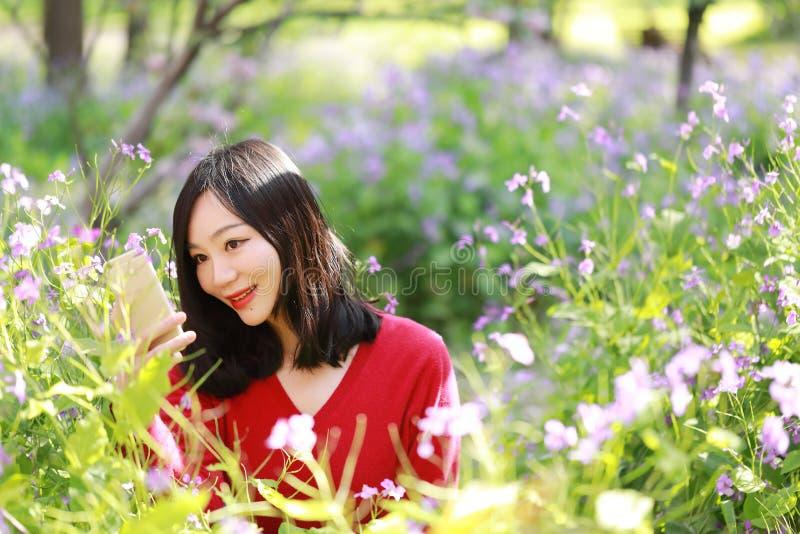 Sonrisa china asiática feliz de la muchacha de la belleza de la mujer en un campo de flor en un selfie del parque del otoño del v fotos de archivo libres de regalías