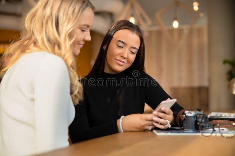 Sonrisa de dos y amigos jovenes hermosos que miran Smartphone en café fotos de archivo libres de regalías