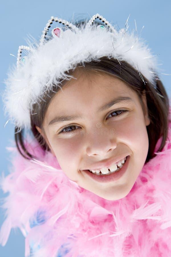 Sonrisa de la boa de la corona y de pluma de la chica joven que desgasta foto de archivo libre de regalías