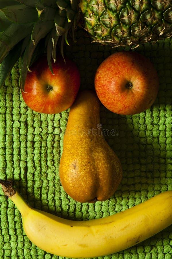 Sonrisa de la fruta de la cara Apple, pera, piña y plátano Fondo verde de la felpa foto de archivo