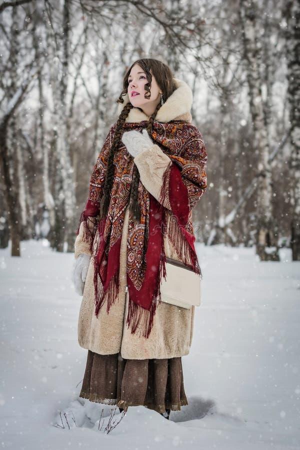 Sonrisa de la muchacha en día de invierno frío al aire libre en un parque nevoso foto de archivo