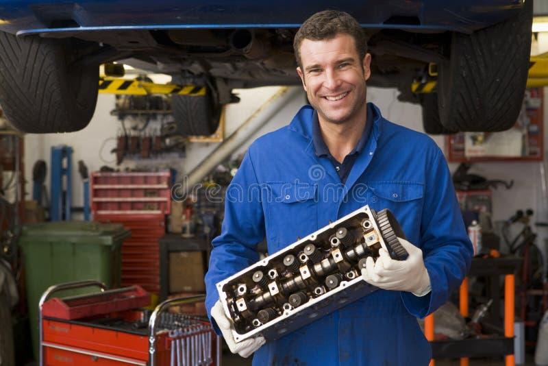 Sonrisa de la pieza del coche de la explotación agrícola del mecánico imagenes de archivo