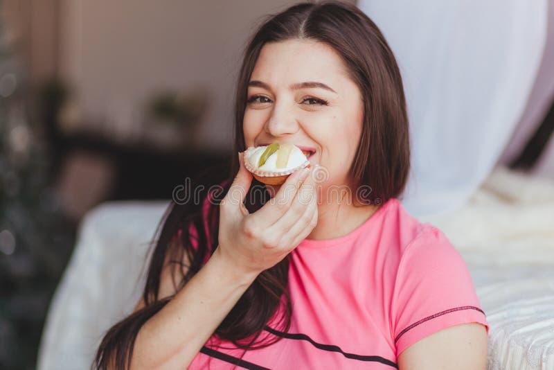 Sonrisa de la torta de la consumición de la mujer embarazada imagen de archivo libre de regalías