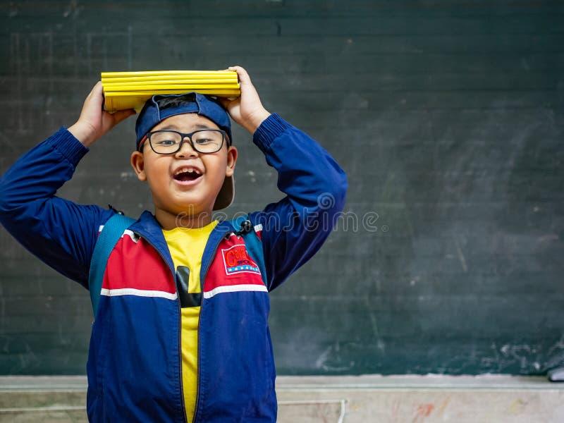 Sonrisa de los vidrios del desgaste del muchacho y soporte felices delante del blackbo fotografía de archivo libre de regalías