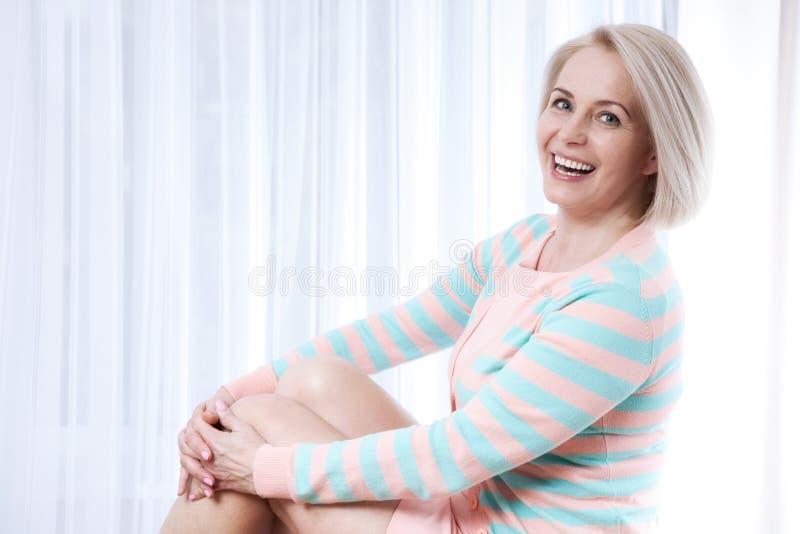 Sonrisa de mediana edad hermosa activa de la mujer amistosa y mirada en la cámara en casa en la sala de estar imagenes de archivo