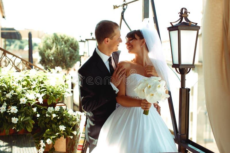 Sonrisa de novia y del novio que mira uno a mientras que se colocan adentro fotografía de archivo libre de regalías
