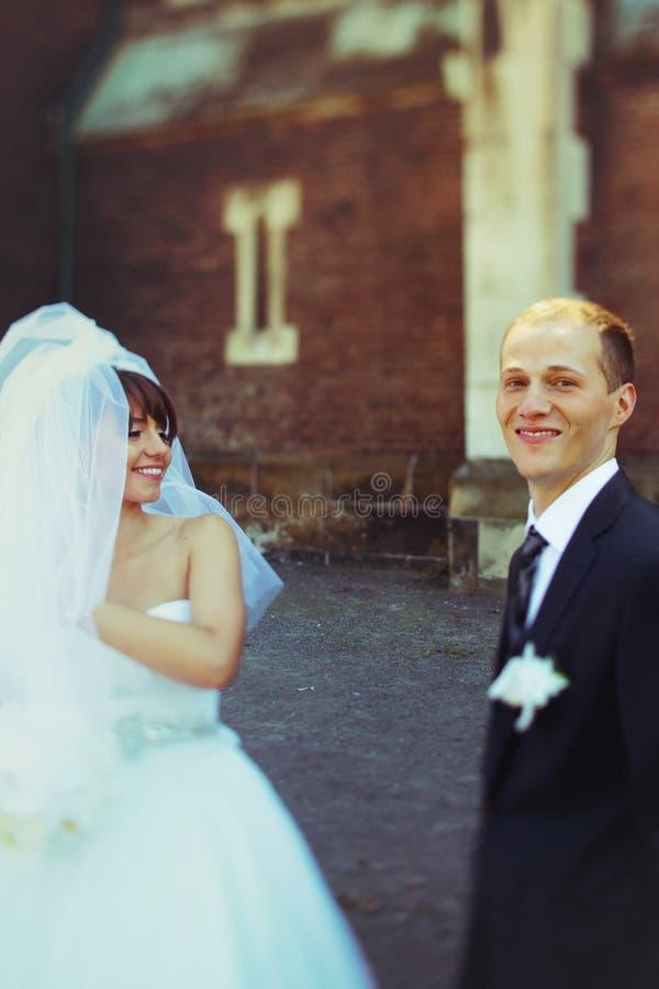 Sonrisa de novia y del novio que se mantiene aparte detrás de una catedral vieja imagen de archivo libre de regalías