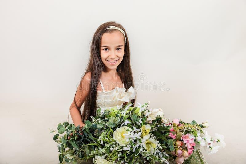 Sonrisa de pelo largo hermosa de la muchacha en su cara hay placer y sorpresa El niño sostiene un ramo enorme de flores en isola fotografía de archivo