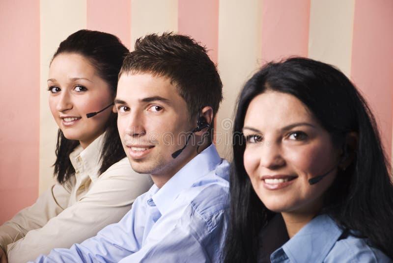 Sonrisa de tres operadores de la ayuda imagen de archivo