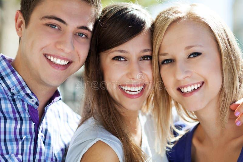 Sonrisa de tres personas jovenes imágenes de archivo libres de regalías