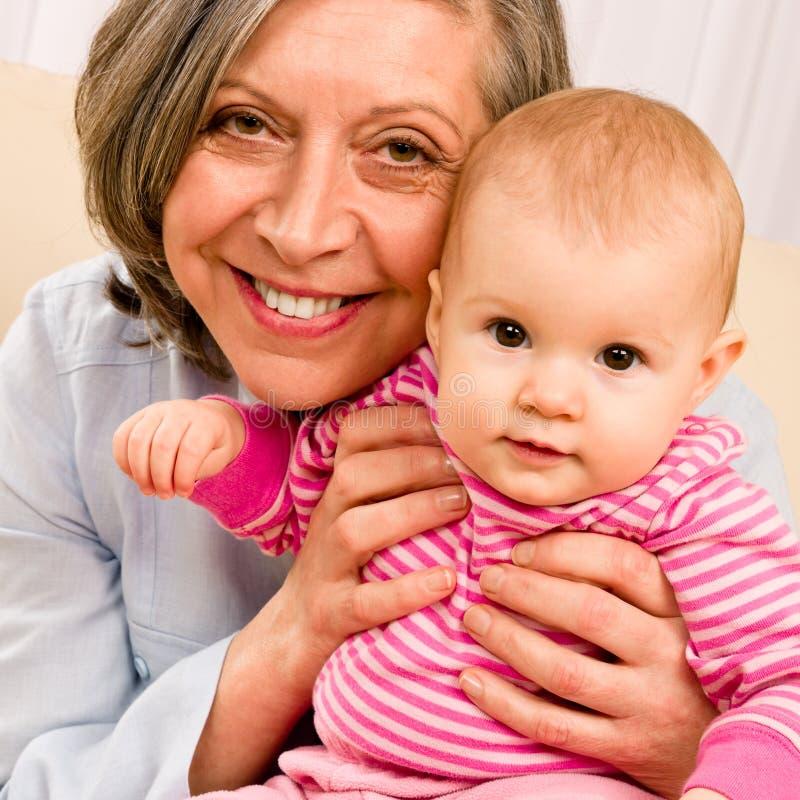 Sonrisa del bebé del asimiento de la abuela pequeña fotografía de archivo