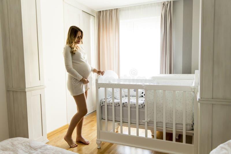 Sonrisa del pesebre del bebé de la creación de la mujer embarazada imágenes de archivo libres de regalías