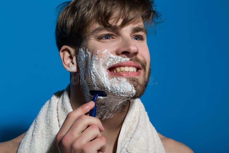 Sonrisa del soltero con crema de afeitar, la maquinilla de afeitar y la toalla fotografía de archivo