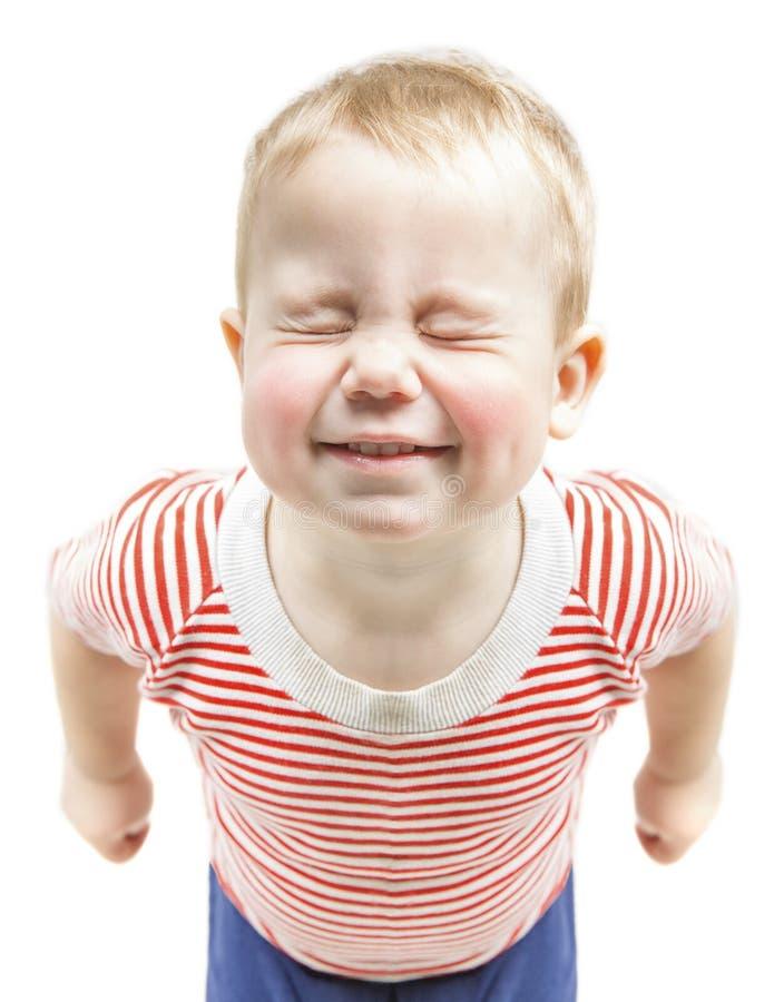 Sonrisa divertida y ojos cerrados estrechos, ha del muchacho del niño fotografía de archivo libre de regalías