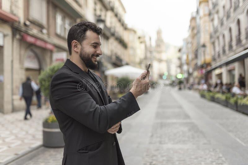 Sonrisa en el hombre del traje del teléfono imagenes de archivo