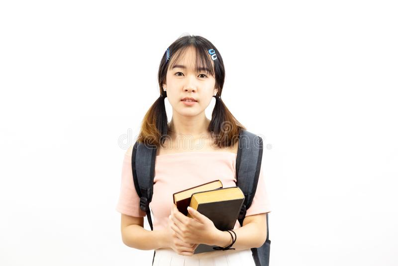 Sonrisa estudiantes universitarios de sexo femenino asiáticos felices y casuales que sostienen la pila de libros con el bolso imágenes de archivo libres de regalías