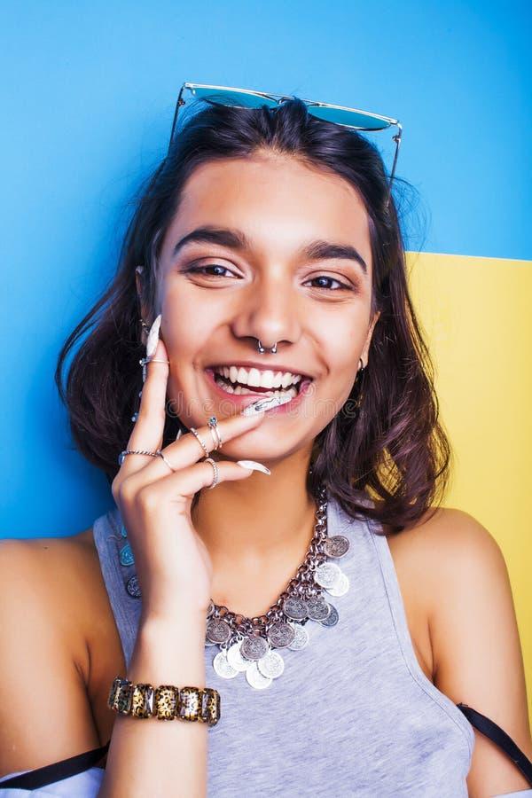 Sonrisa feliz de la muchacha india alegre joven de las razas mixtas, presentando en fondo azul en clothers de la moda del verano  fotos de archivo