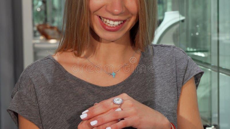 Sonrisa feliz de la mujer, intentando en el anillo de diamante en venta en los joyeros fotos de archivo