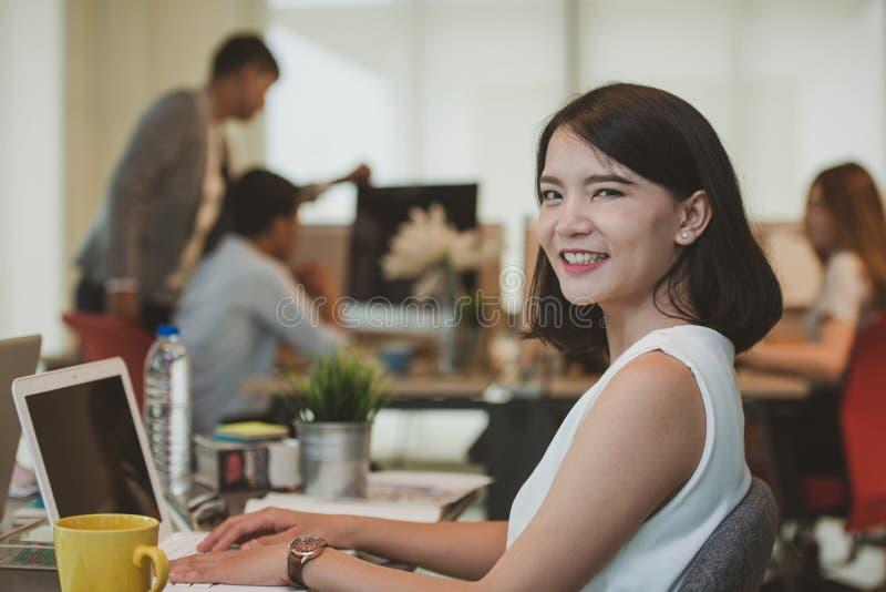 Sonrisa feliz de la mujer joven que trabaja en su escritorio con los colegas en el fondo fotos de archivo