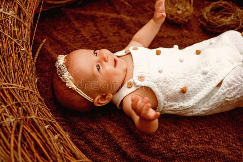 Sonrisa feliz del bebé recién nacido en pesebre de mimbre Bebé recién nacido Niñez temprana Una niñez feliz dura un curso de la v fotografía de archivo libre de regalías