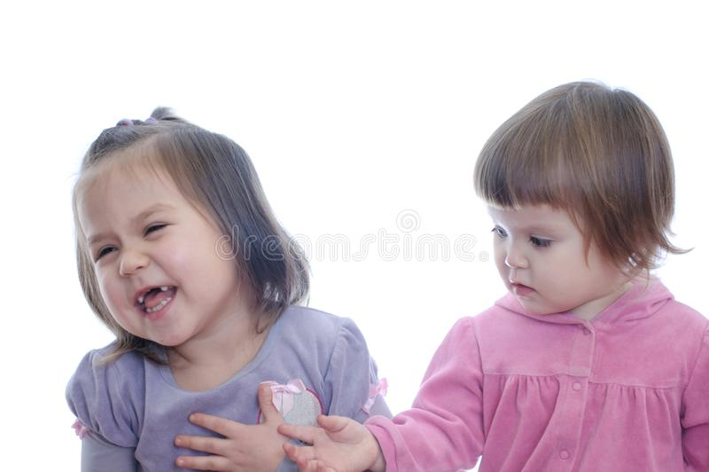 Sonrisa feliz dos niñas aisladas en el fondo blanco hermano con diversa comunicación de la edad imagen de archivo