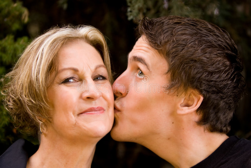 Sonrisa feliz e hijo de la mama que dan beso fotografía de archivo libre de regalías