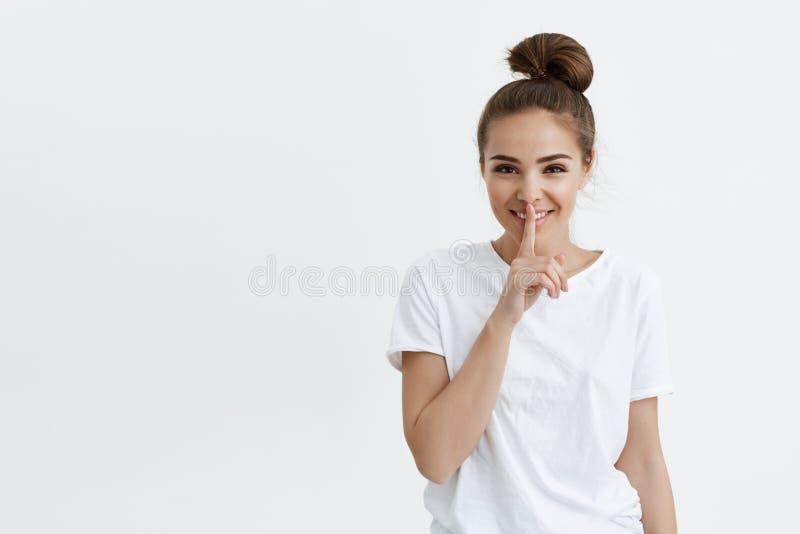 Sonrisa femenina europea de moda alegre mientras que muestra shh gesticule con el dedo índice en los labios, mirando con el posit imagen de archivo