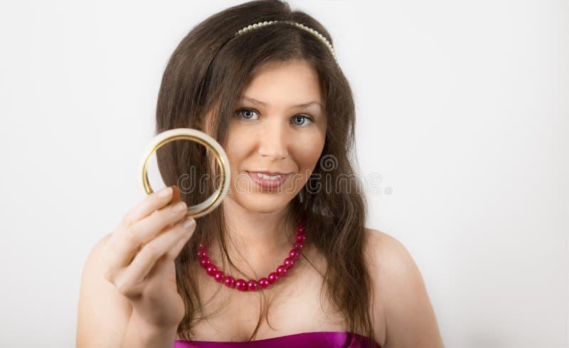 Sonrisa femenina joven alegre y sostener una pulsera imágenes de archivo libres de regalías