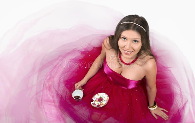 Sonrisa femenina joven alegre y sostener una taza de café imagen de archivo