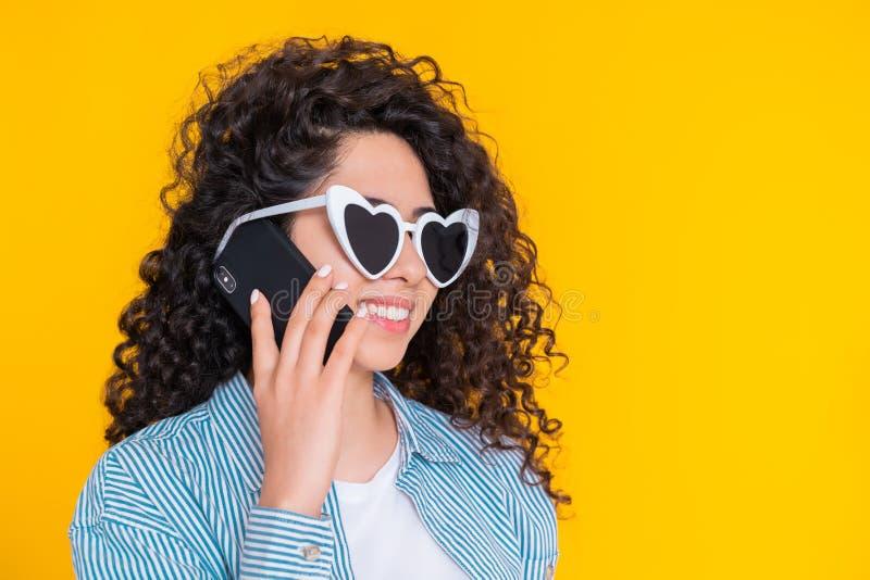 Sonrisa femenina joven y el hablar en el tel?fono m?vil sobre fondo amarillo Muchacha hermosa de la raza mixta que se sostiene y  fotos de archivo