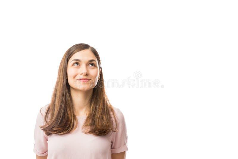 Sonrisa femenina mientras que mira para arriba el espacio en blanco imagenes de archivo