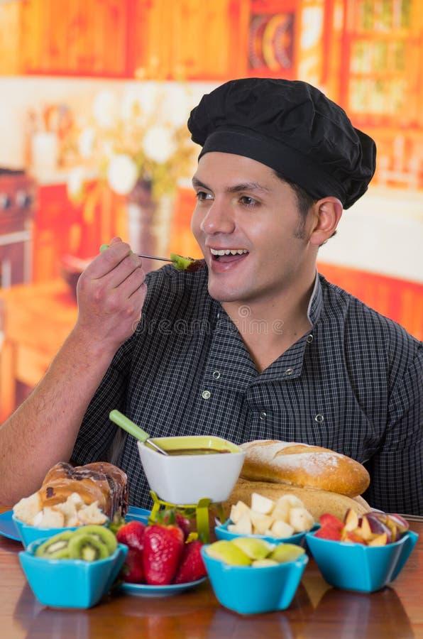 Sonrisa hermosa antropófaga un kiwi delicioso cubierto con la 'fondue' de chocolate dentro de un cuenco blanco con las frutas cla fotografía de archivo