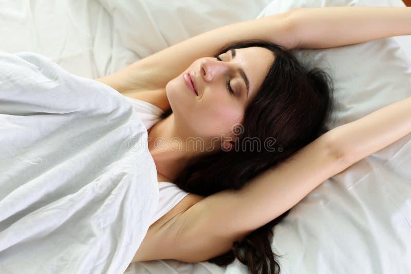 Sonrisa hermosa joven y mujer morena que mienten en cama fotos de archivo libres de regalías