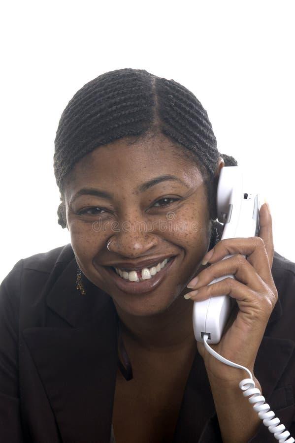 Sonrisa hermosa represenatative del servicio de atención al cliente en el teléfono imágenes de archivo libres de regalías