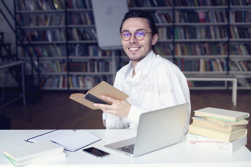 Sonrisa joven del empresario o del estudiante universitario, trabajando en el ordenador portátil que lee un libro en una bibliote fotografía de archivo