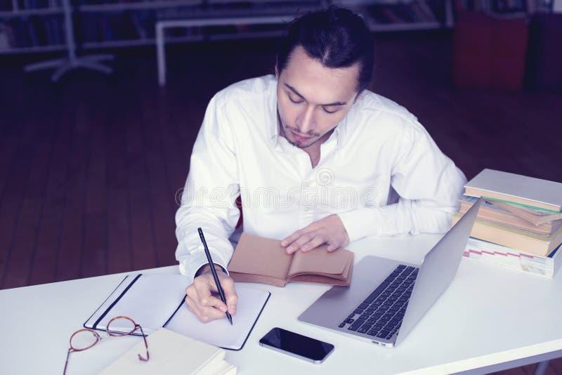 Sonrisa joven del hombre de negocios o del estudiante universitario, trabajando en el ordenador portátil que lee un libro en una  imagen de archivo libre de regalías