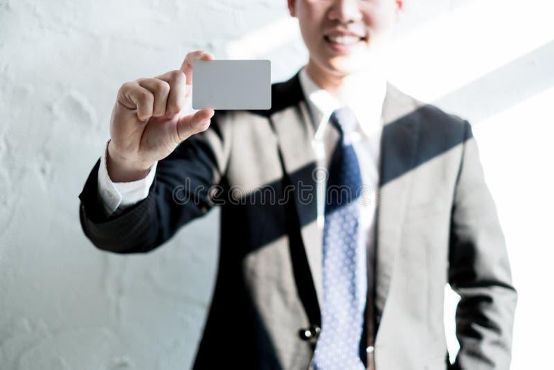 Sonrisa joven del hombre de negocios y sostener la tarjeta de visita en blanco en la oficina, concepto del negocio imagen de archivo libre de regalías
