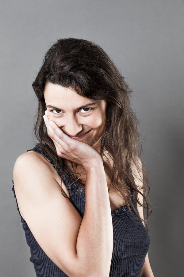 Sonrisa linda de la mujer joven, tocando su cara para la vergüenza foto de archivo