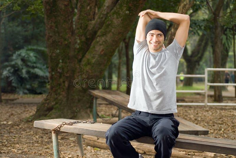 Sonrisa masculina mientras que estira - horizontal fotos de archivo libres de regalías
