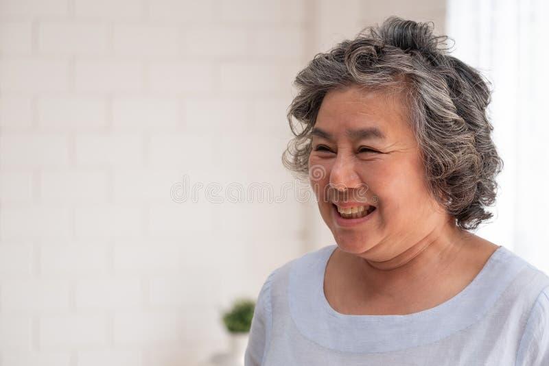 Sonrisa mayor asiática de la mujer en sala de estar en casa, feliz envejeciendo en casa concepto fotos de archivo