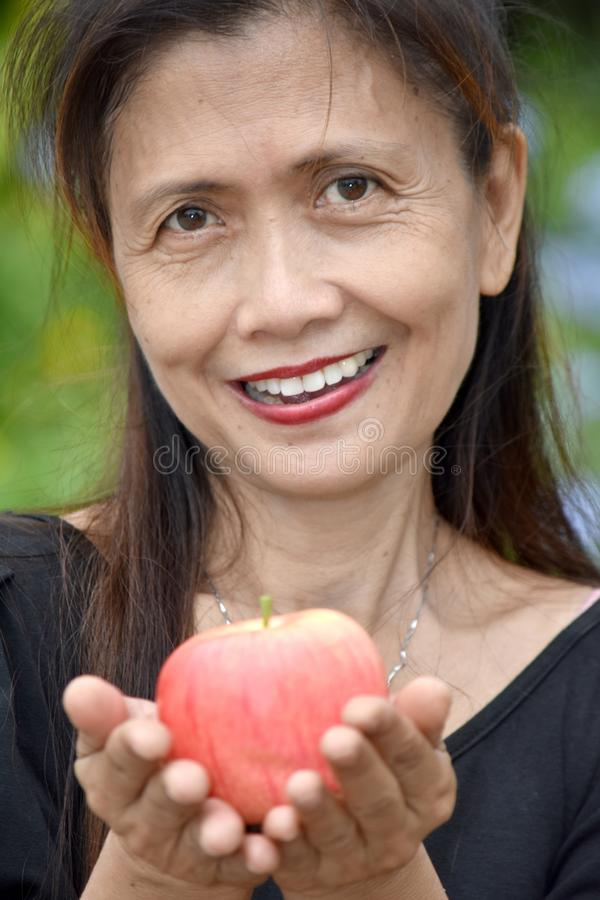 Sonrisa mayor femenina de la minoría con Apple imágenes de archivo libres de regalías