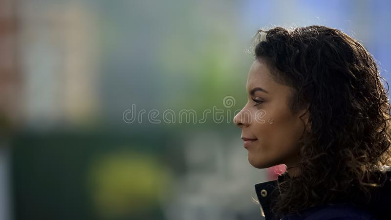 Sonrisa modelo femenina inspirada, retrato biracial hermoso de la señora joven en perfil imagenes de archivo