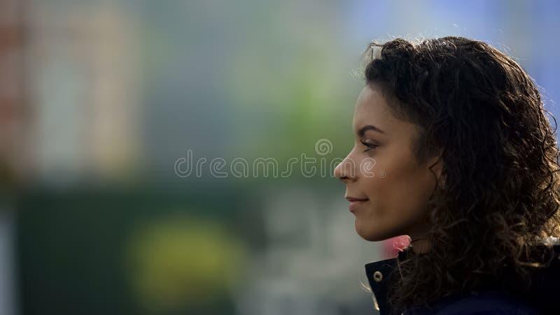 Sonrisa modelo femenina inspirada, retrato biracial hermoso de la señora joven en perfil imágenes de archivo libres de regalías