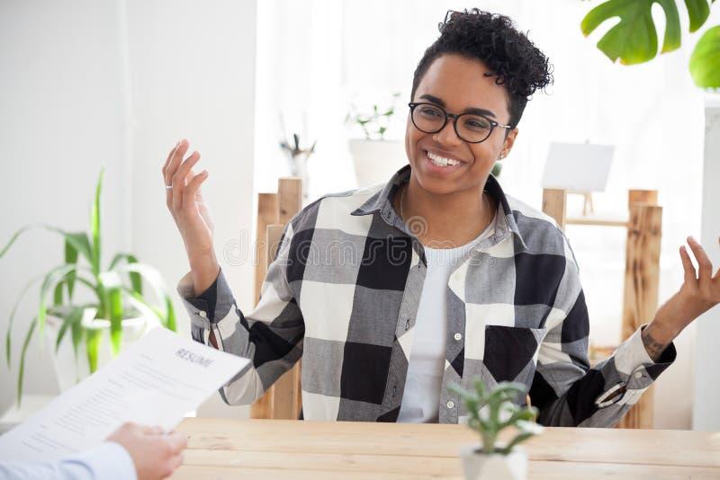 Sonrisa negra feliz de la muchacha que habla en la entrevista de la oficina imagen de archivo