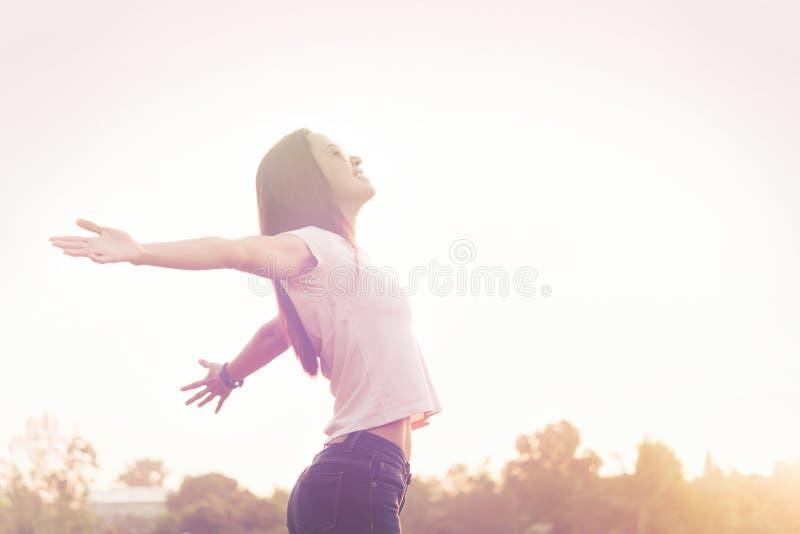 Sonrisa relajante feliz de la mujer joven de la belleza en cielo de la puesta del sol del verano hacia fuera foto de archivo