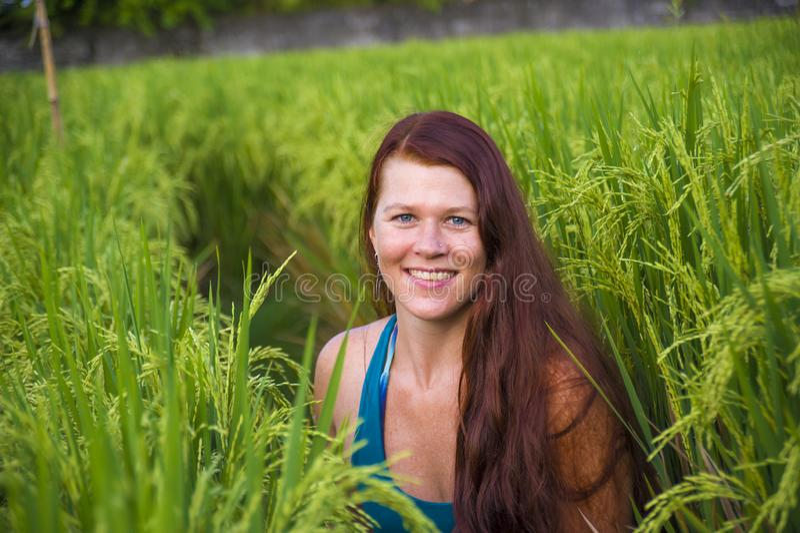 Sonrisa roja feliz y hermosa joven de la mujer del pelo juguetona divirtiéndose que presenta relajado aislado en campo verde del  imagenes de archivo