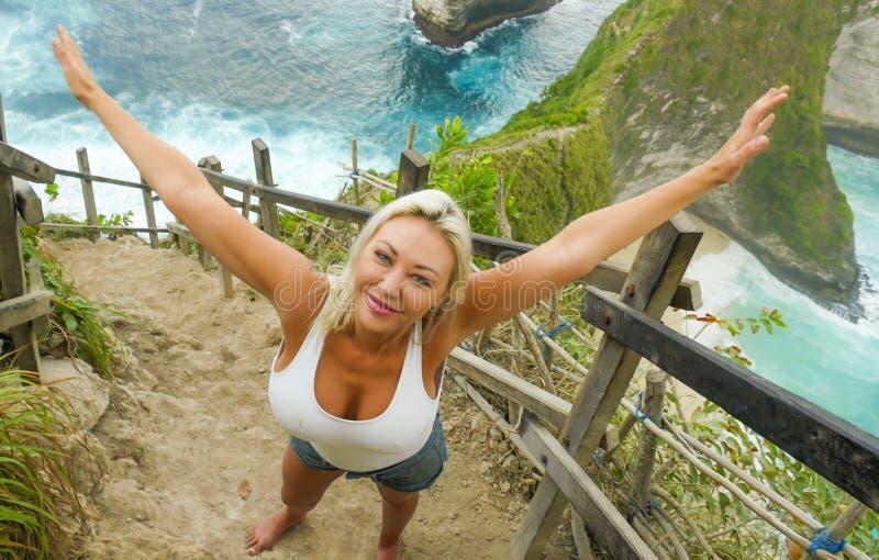 Sonrisa rubia feliz y hermosa joven de la mujer alegre en el paisaje tropical del acantilado de la playa que disfruta de la parti fotos de archivo libres de regalías