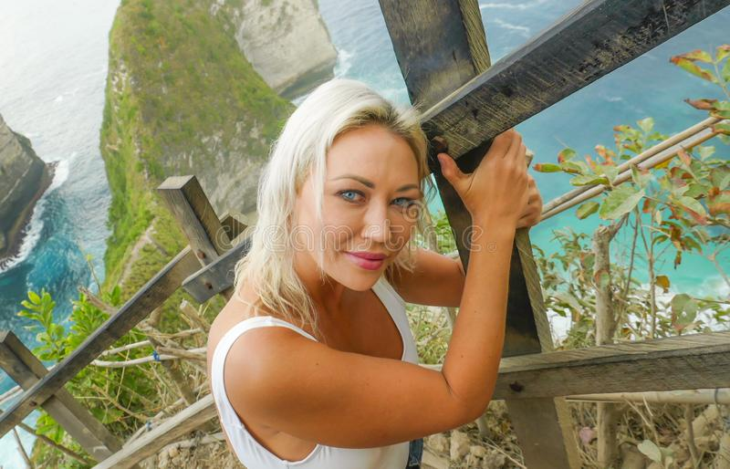 Sonrisa rubia feliz y hermosa joven de la mujer alegre en el paisaje tropical del acantilado de la playa que disfruta de la parti foto de archivo